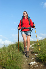 Woman with backpack and trekking poles