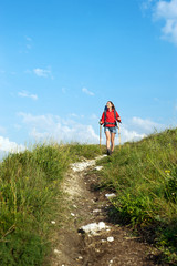 Young woman with backpack and trekking poles