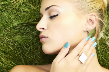 Beautiful blond girl sleeping on green grass. beauty woman