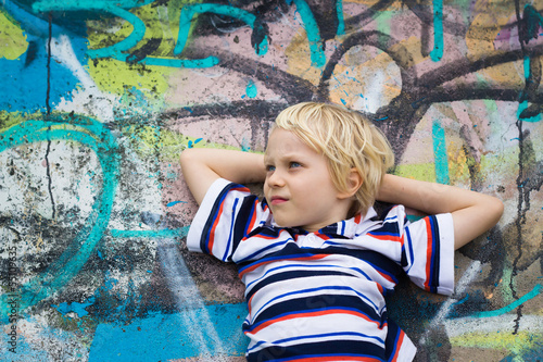 Handsome boy in deep thought against a graffiti wall
