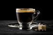 Espresso in Glastasse mit Löffel, Zucker und Kaffeebohnen