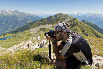 Young photographer taking landscape pictures in the mountains