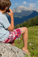 Jugendlicher telefoniert aus dem Berg Urlaub nach Hause