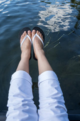 Feet Wearing White Flipflops Hanging Over a Lake