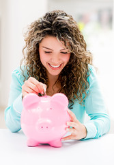 Woman putting savings in a piggybank