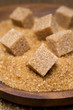 demerara sugar and brown sugar cubes in a bowl, selective focus