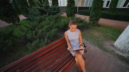 girl sitting on a bench near the university
