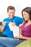 Couple eating Asian food. Cheerful young couple eating Asian foo