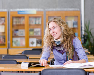 female student with tablet computer in library. looking away