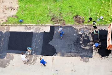 workers laid asphalt on urban road