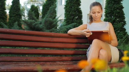 girl sitting on a bench near the university with tablet