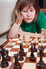 little girl playing chess lying on couch