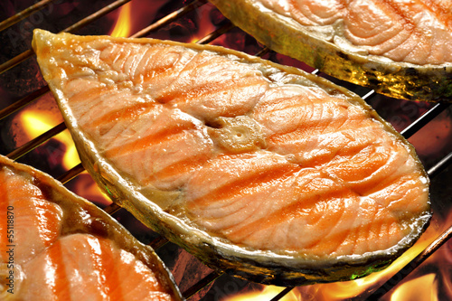Pieces of salmon on flaming grill
