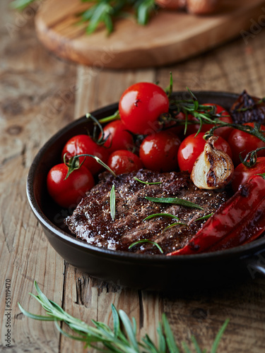 Grilled steak with vegetables in a pan