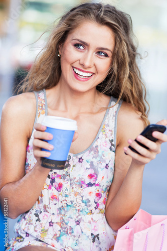 Woman with coffee and mobile phone