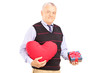 Mature gentleman holding a red heart and a gift