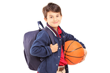 Schoolboy with backpack holding a basketball