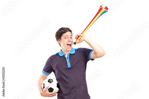 Male sport fan holding a football and horn