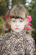 Serious little girl with pink bows in overcoat looks at camera i