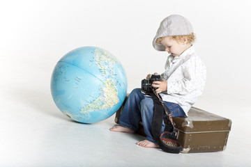 Toddler with old camera and suitcase