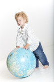 Toddler with a globe isolated on white