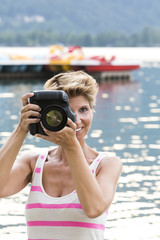 Young woman W34 on vacation takes a picture with her DSLR