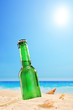 Beer bottle on a sandy beach, with clear sky and sun, next to th