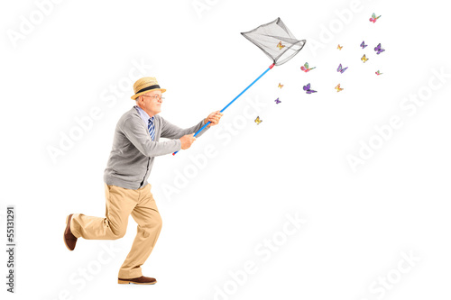 Mature man running and catching butterlies with net