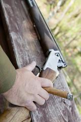 Male hand holding cigar with handgun in background