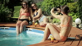 Female friends on summer holidays taking photo with cellphone