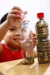 Little Boy Putting Money In a Bottle