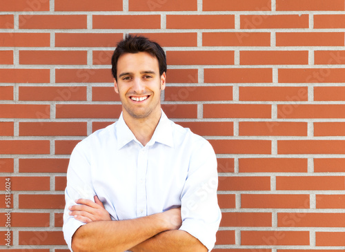 Handsome latin guy in front of a brick wall