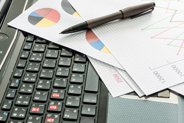 labtop , financial charts , Document file , pen on the table