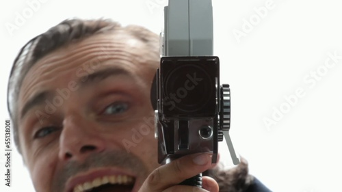 man with old movie camera over white background