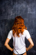 Redhead woman by blank blackboard
