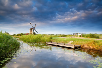 windmill on riverside with reflected sky