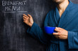 Man in robe pointing at breakfast menu on blackboard