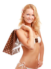 A beautiful woman wearing a swimsuit, holding a shopping bag