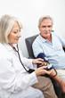 Ärztin misst Blutdruck bei Senioren