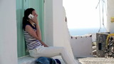 Beautiful woman talking on mobile phone on Santorini