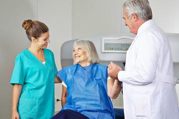 Arzt und MTA helfen Seniorin in Radiologie