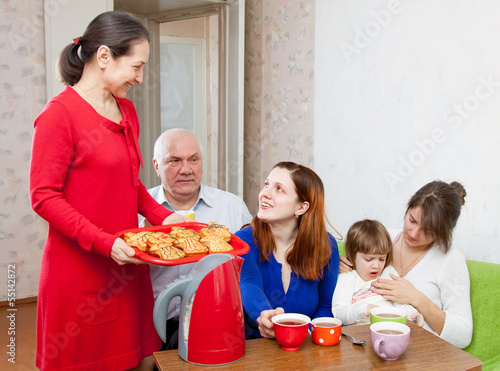 family having breakfast with cakes