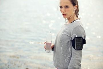 Serious Female Runner Holding Bottled Water