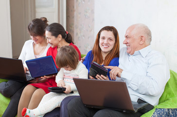 family enjoys on sofa with few laptops