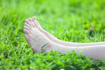 Barefooted beautiful female feet on green grass
