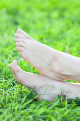 Barefooted female feet on grass vertical frame