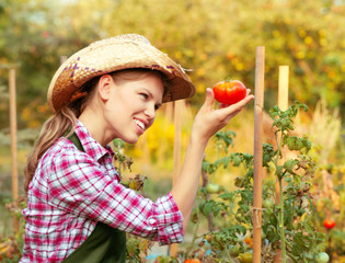 Cheerful woman gardener looking at ripe red tomato