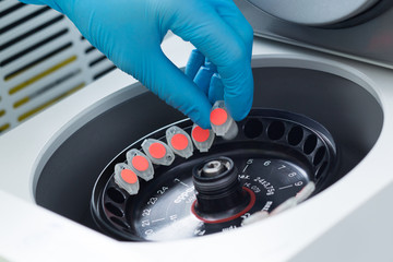 Scientist loading a sample to centrifuge