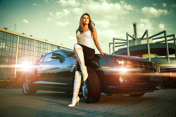 beautiful woman stands in front of sport car