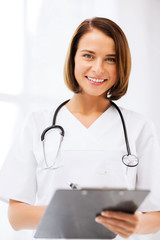 doctor with stethoscope writing prescription